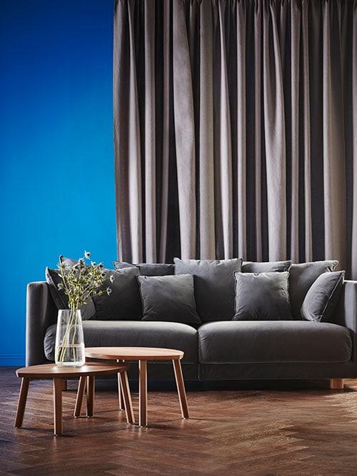 Un canapé gris avec deux tables basses gigognes à la finition effet noyer.