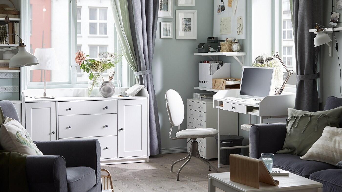 Un canapé gris foncé, un bureau blanc avec un ordinateur dessus, une chaise pivotante beige, des étagères blanches avec des documents et des armoires blanches.