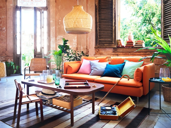 Un canapé orange avec des coussins de différentes couleurs, derrière une table basse brun foncé.