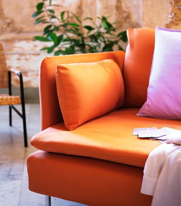Un canapé orange avec un coussin rose et un plaid rose clair. Quelques cartes à jouer sont posées sur le canapé.