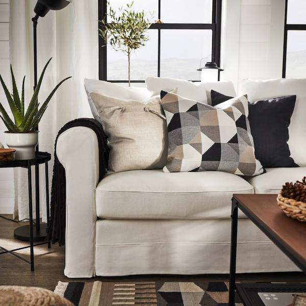 Un canapé où sont posés un jeté gris et divers coussins décoratifs aux couleurs neutres.