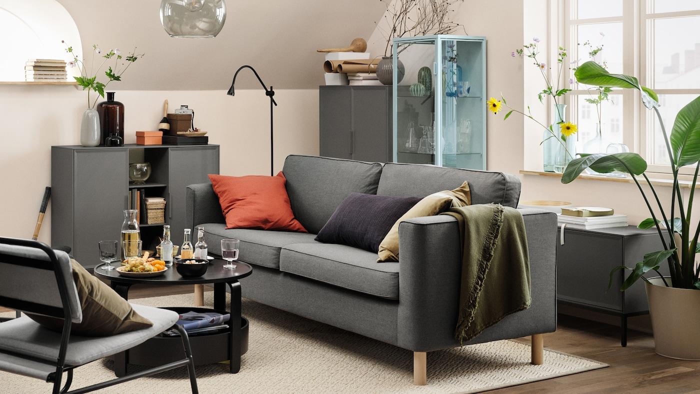 Un canapé PÄRUP gris avec troiscoussins dans un séjour beige. Une table basse avec des boissons et des en-cas se trouve devant.