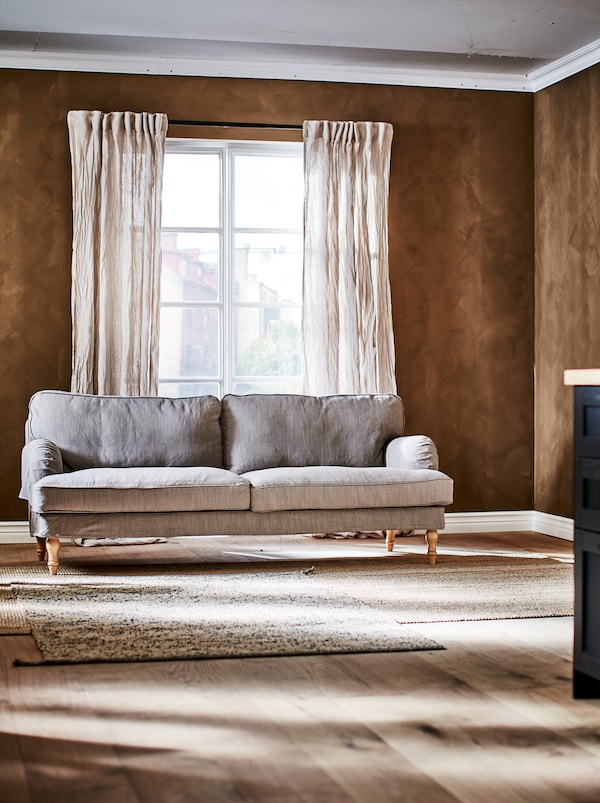 Un canapé STOCKSUND dans une pièce aux murs bruns avec des portes-fenêtres et des accessoires aux textures naturelles.