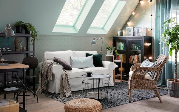 Un canapé traditionnel EKTORP 2 places en Vittaryd blanc face à un fauteuil en osier BYHOLMA/MARIEBERG dans un petit salon vert clair, gris et blanc avec toit mansardé.