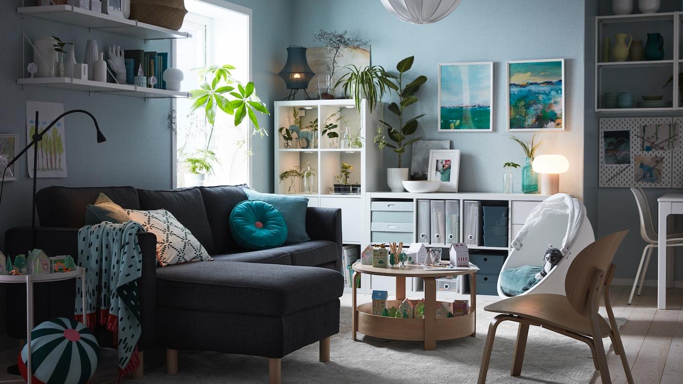 Un canapé trois places avec méridienne, une étagère avec portes, un fauteuil pivotant, une table basse et des jouets.