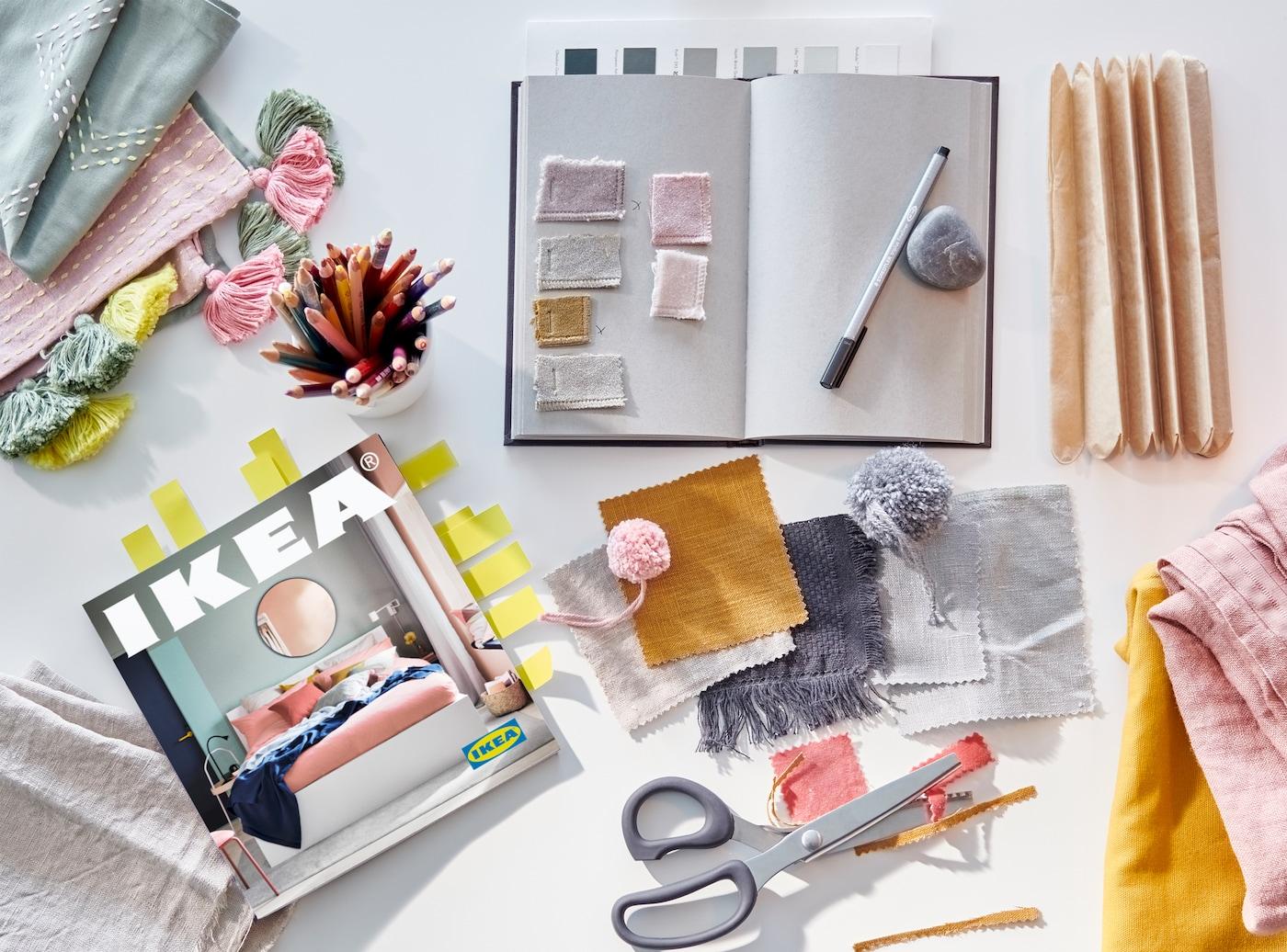 Un carnet de notes, un stylo, des ciseaux et des morceaux de tissu en rose, gris, jaune, moutarde et vert à côté d'un catalogue IKEA 2021.