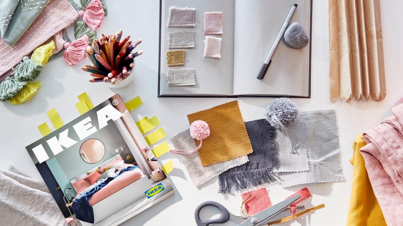 Un carnet pour noter des idées, une paire de ciseaux, des morceaux de tissu dans des pastels clairs et des tons moutarde chaleureux, et un Catalogue IKEA 2021.