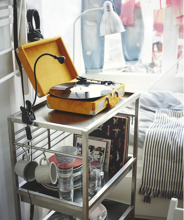 Un carrello di metallo con un giradischi e un faretto con morsetto sul ripiano superiore, piatti, tazze e bicchieri sui ripiani sottostanti – IKEA