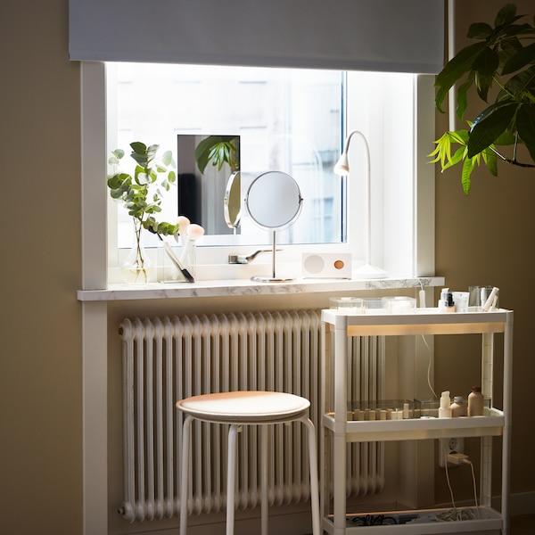 Un carrello VESKEN bianco e uno sgabello MARIUS bianco davanti a una finestra con diversi oggetti sul davanzale.