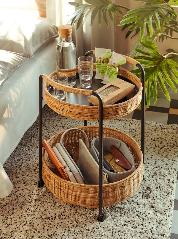Un cărucior LUBBAN din ratan cu un nivel pe care sunt gustări și o carafă IKEA 365+ cu apă și alte obiecte personale.