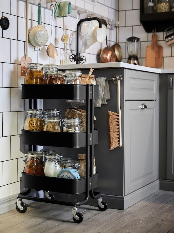 Un cărucior negru, RÅSKOG, cu borcane de sticlă cu diverse alimente pe polițele sale, lângă o chiuvetă într-o bucătărie cu gresie albă.