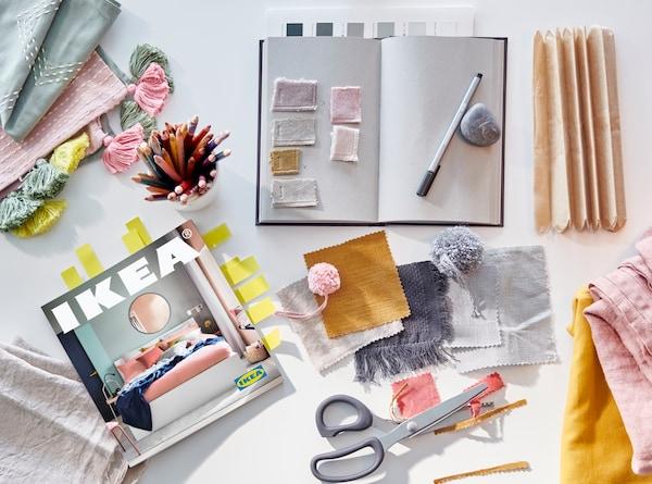 Un Catalogue IKEA 2021, un carnet pour noter des idées, une paire de ciseaux, des morceaux de tissu dans des pastels clairs et des tons moutarde.