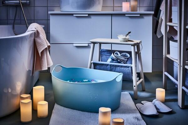 Un cesto para a coada TORKIS empregado como baño de pés, rodeado de candeas LED, nun baño.