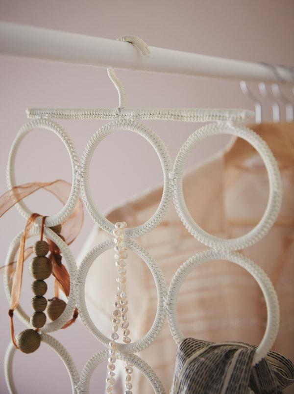 Un cintre multiusage KOMPLEMENT suspendu à une tringle à vêtements accueille des colliers, un foulard et d'autresaccessoires.