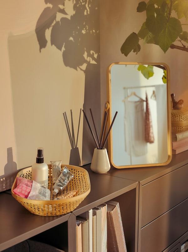 Un coin beauté sur une bibliothèque basse: des bouteilles dans une corbeille en bambou KLYFTA, des bâtonnets diffuseurs NJUTNING et un miroir IKORNNES.