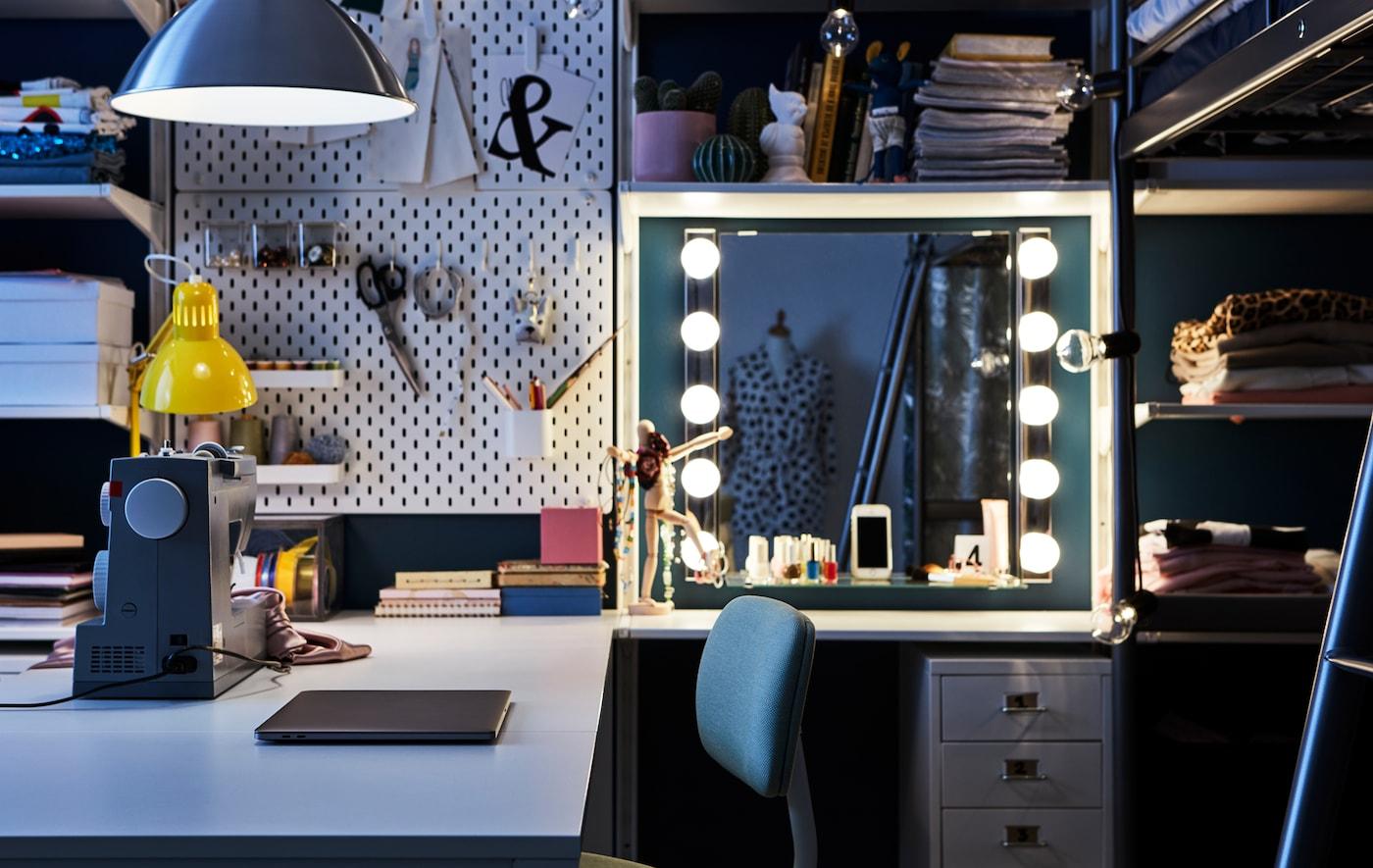 Un coin bureau dans la chambre à coucher avec un bureau, une machine à coudre, une zone maquillage et un panneau perforé IKEA SKÅDIS.