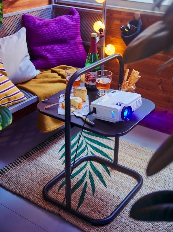 Un coin de balcon avec de quoi boire et grignoter et un petit projecteur sur une table d'appoint HUSARÖ, devant un banc tonnelle SVANÖ garni de coussins.