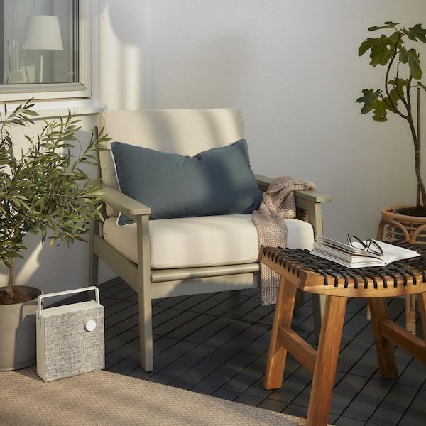 Un coin de balcon avec un fauteuil gris et des coussins blancs, un tabouret en bois, une enceinte blanche et un plaid rose.