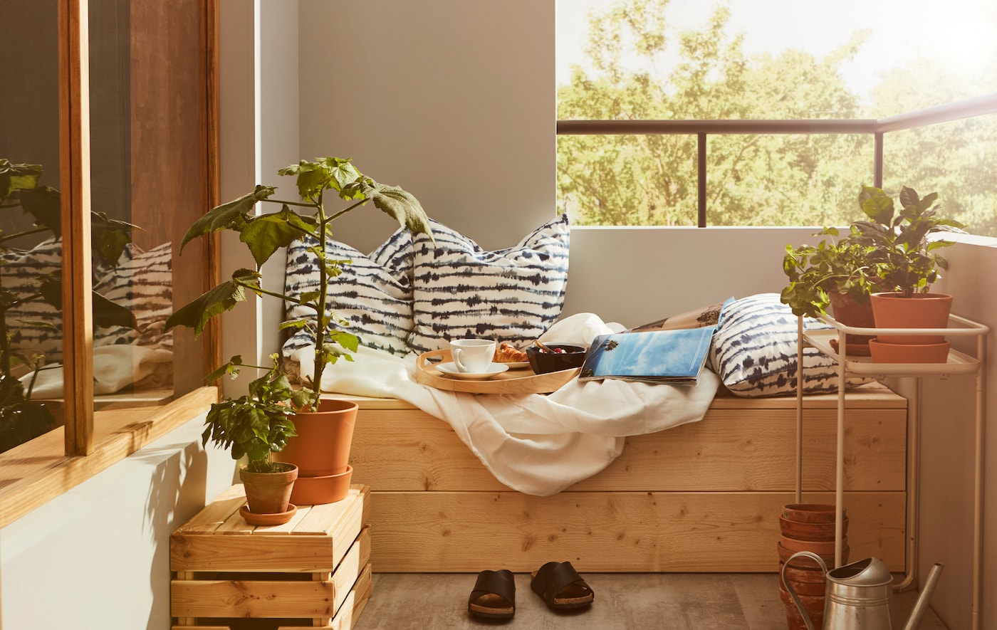 Un coin de balcon avec une assise en bois sur laquelle se trouvent des coussins, du linge de lit et un plateau avec un petit déjeuner léger.