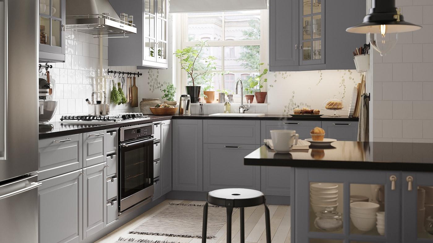 Un coin de cuisine avec des armoires grises, un comptoir à effet minéral noir, un évier blanc, une table de cuisson au gaz et un îlot de cuisine.