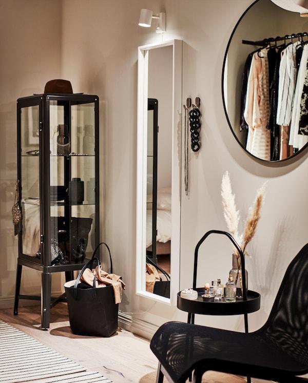 Un coin dressing élégant avec un miroir en pied blanc, une applique, des crochets portant des colliers et une table d'appoint avec des flacons de parfum.