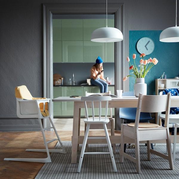 Un comedor con sillas mezcladas que lleva a una cocina en la que hay una persona sentada en la encimera.