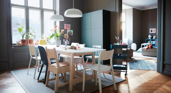 Un comedor con sillas multicolor alrededor de una mesa con la superficie blanca y una combinación de almacenaje gris/turquesa IKEA BESTÅ.