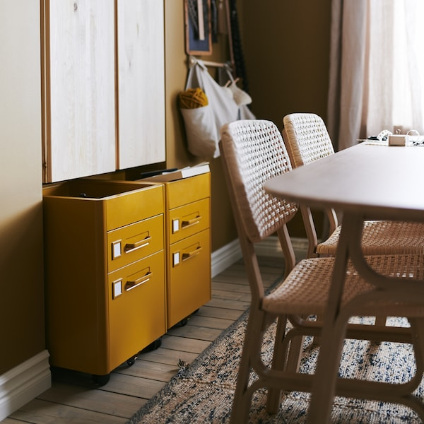 Un comedor en tonos marrones con dos cajoneras IDÅSEN en marrón dorado apoyadas contra una pared detrás de una mesa y sillas.