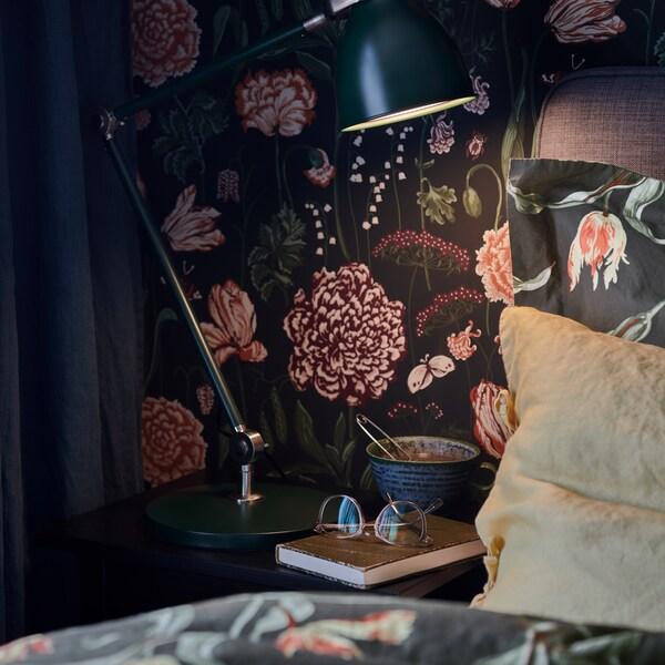 Un comodino con lampada da lavoro ARÖD, una tazza e un libro con sopra un paio di occhiali - IKEA