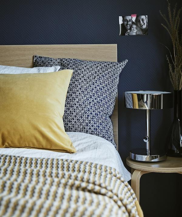 Un comodino con una lampada da tavolo vicino al letto in una camera dalle pareti blu scuro - IKEA