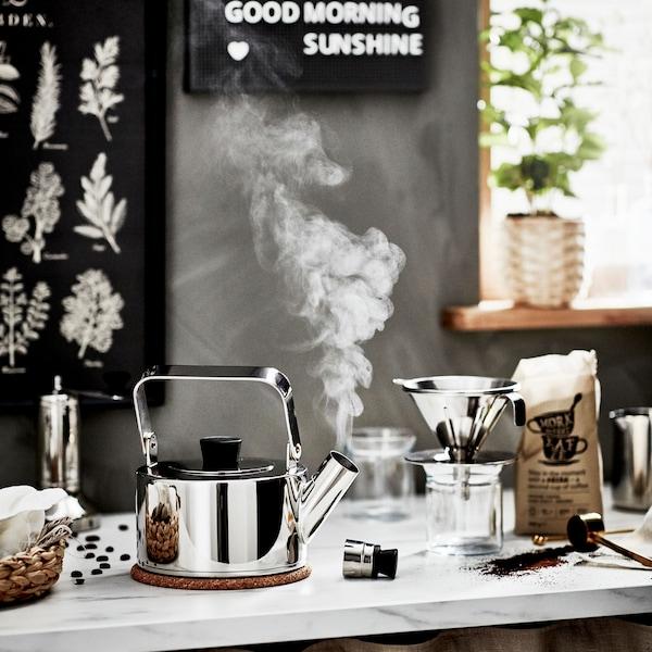 Un comptoir de cuisine en marbre et une bouilloire en marche, un filtre à café en métal et un sac de café PÅTÅR ouvert.
