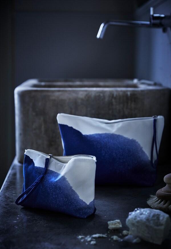 Un conjunto de dos bolsas de accesorios IKEA TÄNKVÄRD en blanco y azul profundo colocadas en el suelo bajo una iluminación tenue.