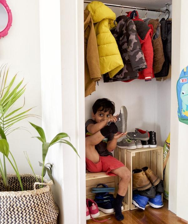 Un copilaș care se încalță și care stă pe o băncuță de lemn sub hainele atârnate într-un dulap de vase.