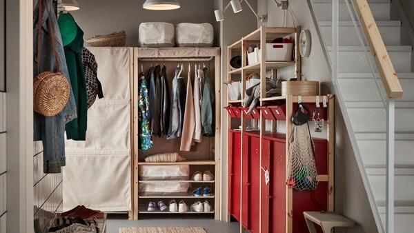 Un couloir avec des étagères et des rangements IVAR, y compris des armoires et des tiroirs rouges, où sont rangés des vêtements, des chaussures et des articles ménagers.