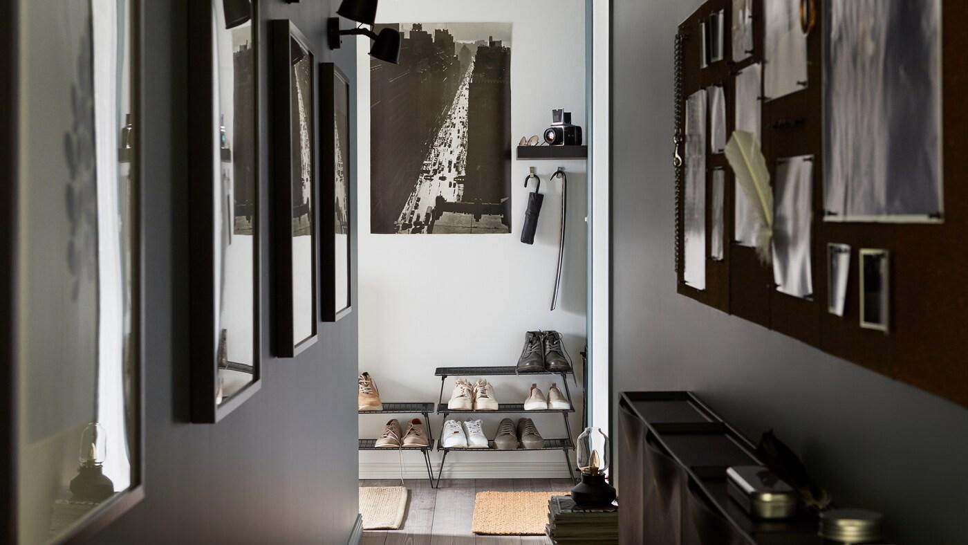 Un couloir étroit avec des photos sur les murs, des rangements pour chaussures à armature noire empilés les uns sur les autres, un tableau d'affichage noir.
