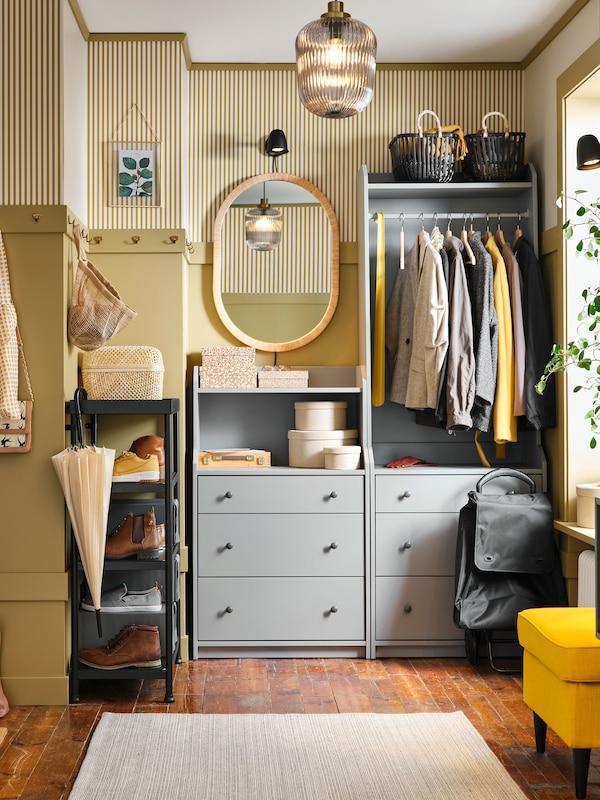 Un couloir jaune comprenant une armoire-penderie ouverte et une commode à tiroirs. Des manteaux sont sur le rail et un miroir se trouve à côté.