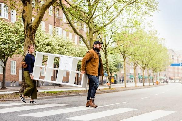 Un couple porte un KALLAX et traverse une rue arborée en ville.
