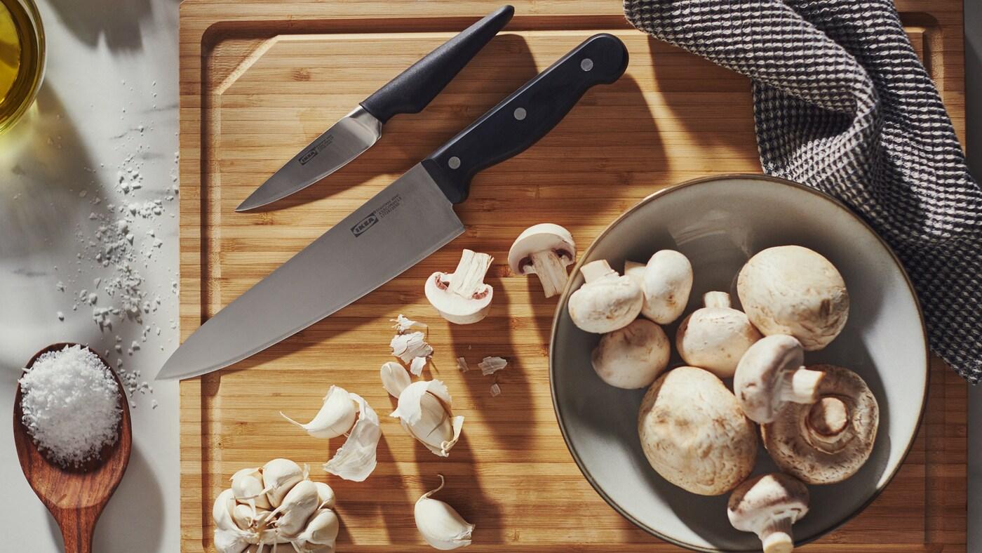 Un couteau de chef VARDAGEN, un couteau d'office VÖRDA et de l'ail sur une planche à découper en bambou, en plus d'un bol avec des champignons.