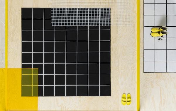 Un covor negru cu linii albe și un covor alb cu linii negre, pe o podea din lemn deschis la culoare, cu pantofi galbeni.