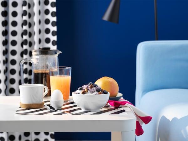 Un cuarto coa parede azul, unha mesa branca, lista para o almorzo, cunha cunca de cereais, café e zume de froitas.