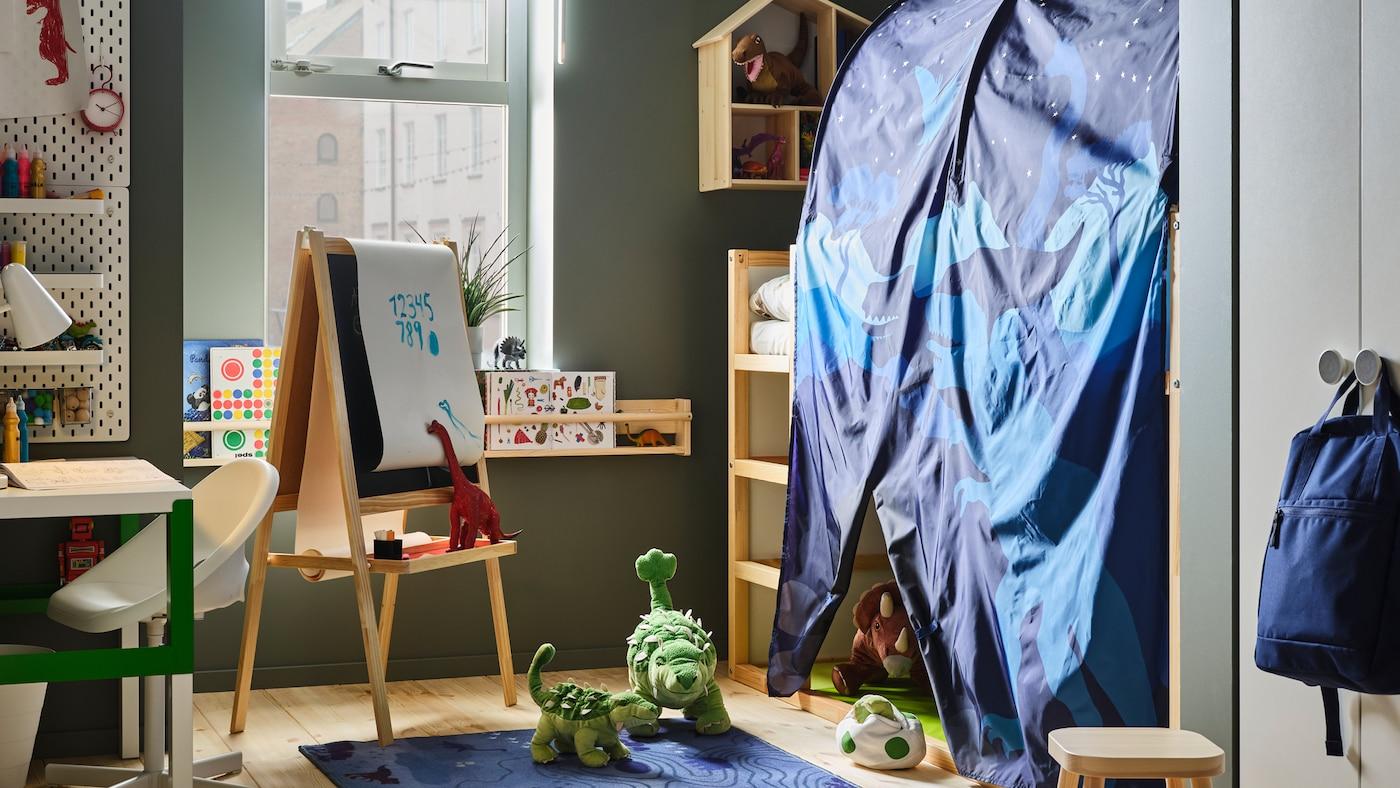 Un cuarto infantil cunha cama reversible e un dosel con cortina KURA e moitos dinosauros de xoguete. Hai un cabalete MÅLA preto da cama.