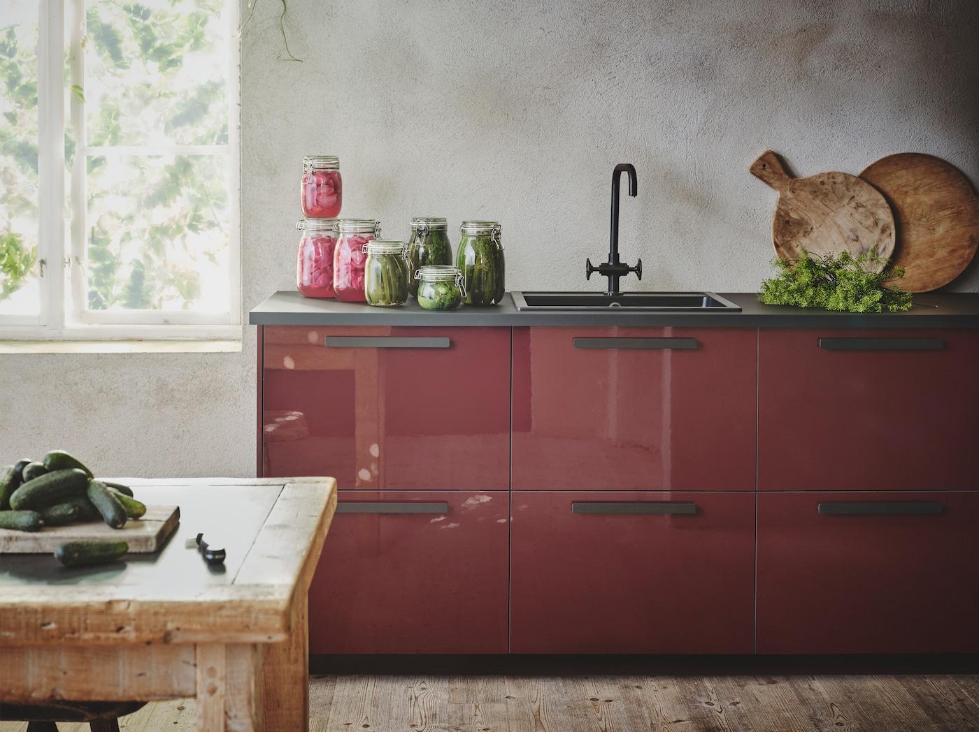 Un cuina de color vermell fosc brillant amb taulell, poms i aigüera de color negre, instal·lada en un ambient rústic amb parets d'estucat gris.