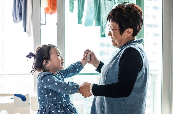 Un dame debout tenant par les mains une petite fille