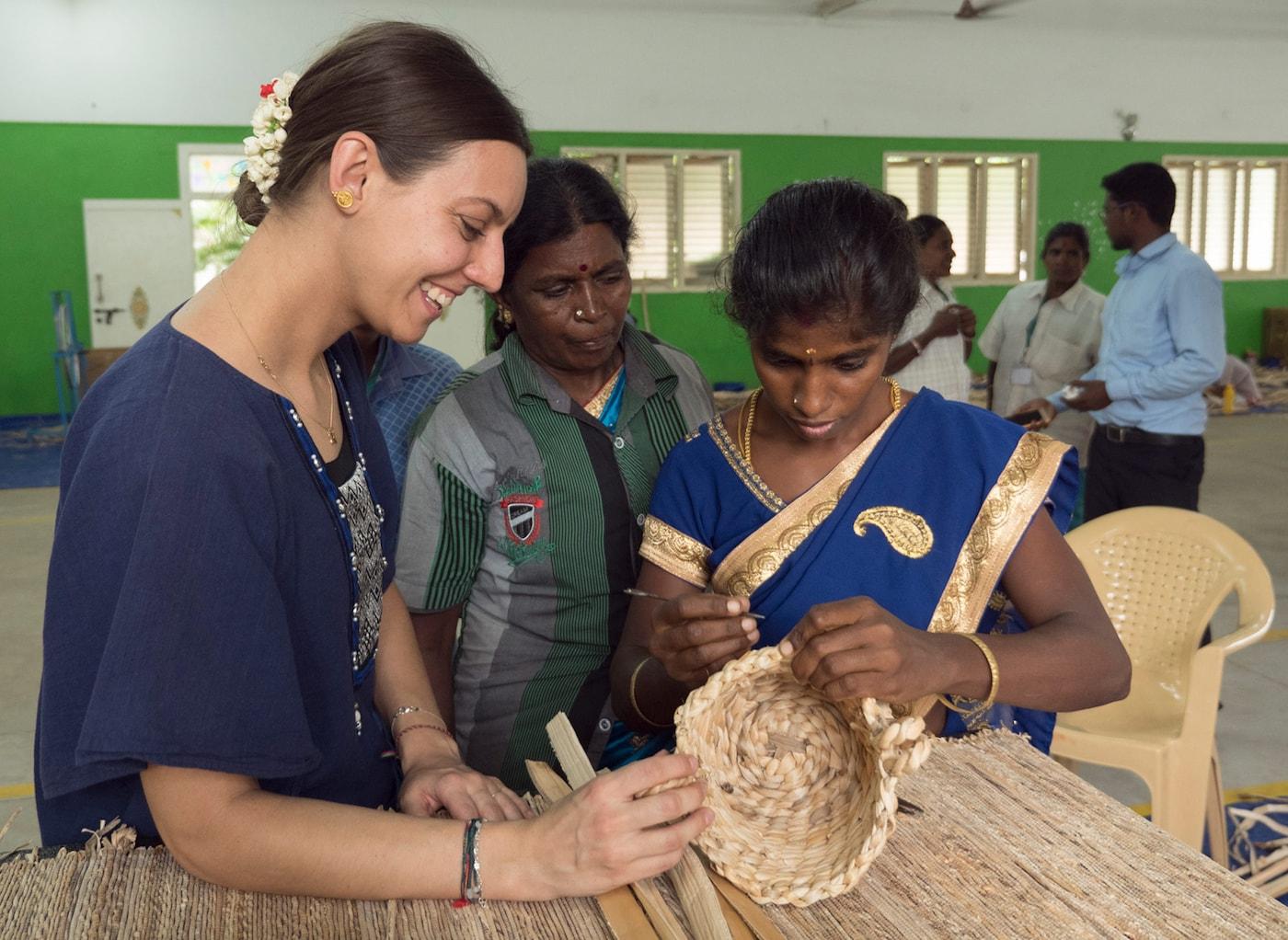 Un designer IKEA et des artisans indiens observant un panier tissé à la main, et discutant les techniques de tissage.