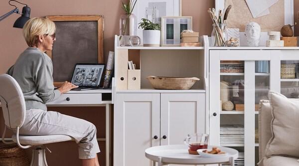 Un dessus de bureau blanc avec un ordinateur portable, une liste, un crayon, des photos, des échantillons de peinture de couleur et des échantillons de tissu posés dessus.