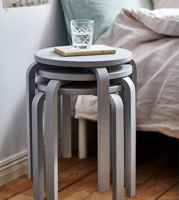 Un detalle de tres taburetes apilados de color gris que se usan como mesilla.