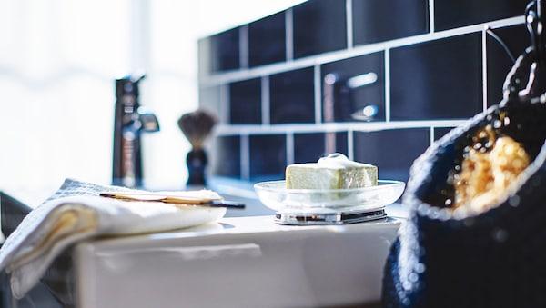 Un detalle de un lavabo blanco, con jabón en un recipiente y una cuchilla de afeitar en una toalla.