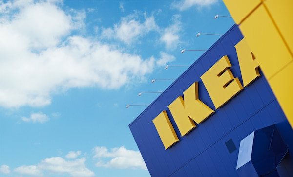 Un día despejado y soleado donde se aprecia una esquina de la icónica tienda de IKEA, con sus colores azules y amarillo. Se aprecia el logo grande.