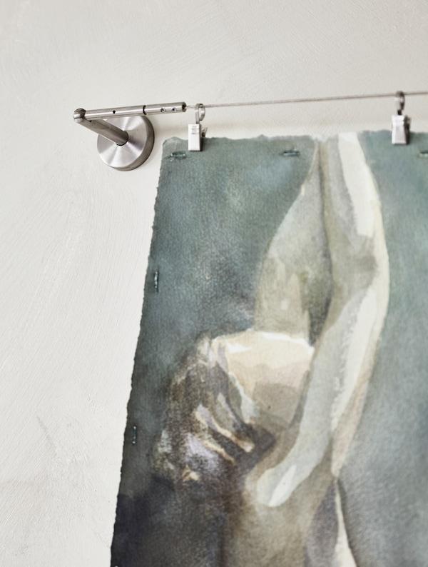 Un dibujo hecho con acuarelas colgado en un cable de acero para cortina.