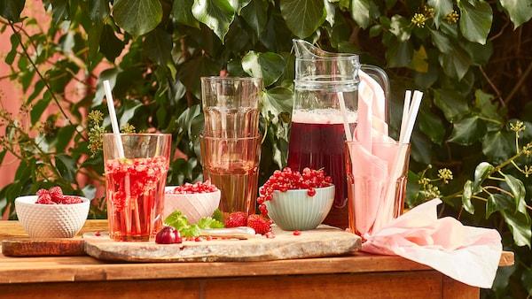 Un distributeur de boissons à l'extérieur avec un pichet de jus rouge et des verres clairs rose pâle.
